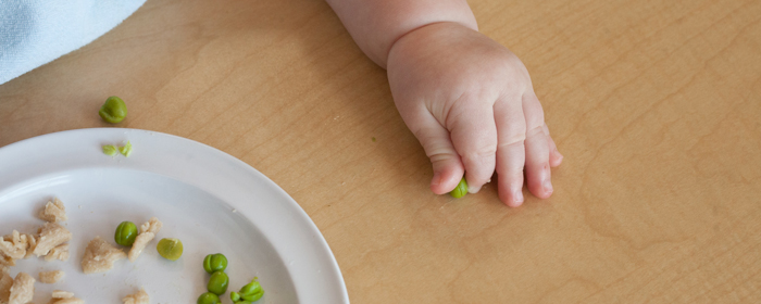 Baby hand grabbing a small pea on a wooden table with a plate nearby.